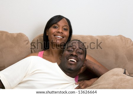 Happy, attractive couple on a couch. He is lying across her lap and laughing. Horizontally framed photograph. Both are looking at the camera and laughing.