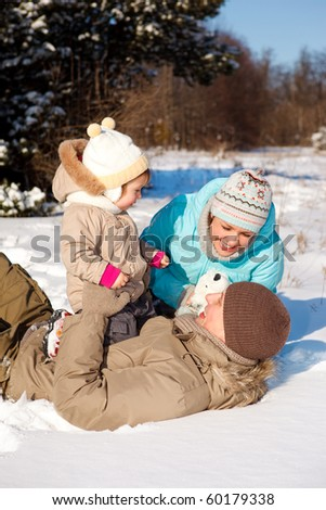 Happy attractive family playing on snow - stock photo