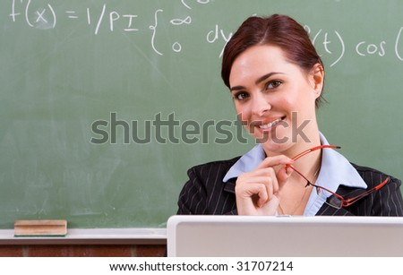 happy attractive female teacher sitting in front of blackboard