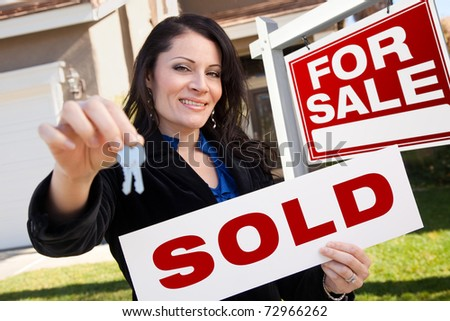 Happy Attractive Hispanic Woman Holding Sold Real Estate Sign and Keys in Front For Sale Real Estate Sign and House. - stock photo