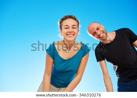 happy attractive man and woman looks into the camera on the sunny beach over the blue sky. Focus on the man