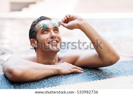 Happy attractive man in sunglasses resting relaxed on edge of swimming pool