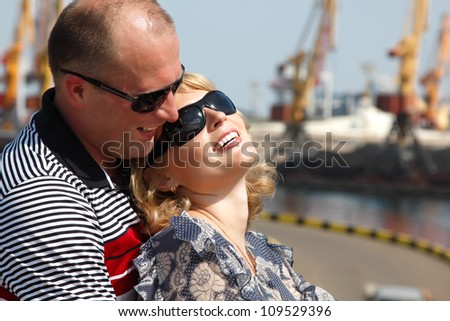 Happy attractive mid adult couple have fun outdoor. Wife and husband in port