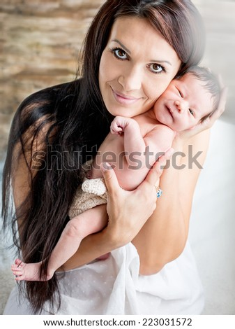 Happy attractive mother holding newborn baby on a white background