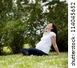 Happy attractive pregnant woman in park leaning back enjoying the sun - stock photo