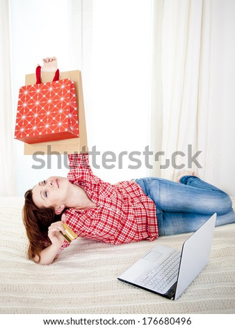 happy attractive red haired  woman wearing a red shirt  lying on her bed on her laptop online shopping on white background