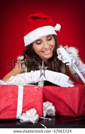 happy attractive santa woman wrapping Christmas presents - stock photo