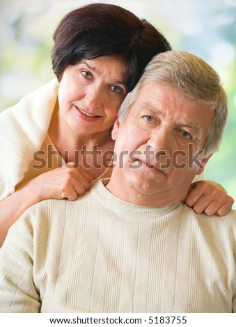 Happy attractive senior couple embracing together outdoors