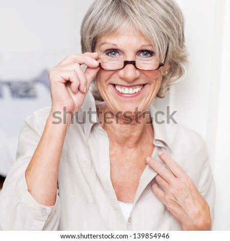 Happy attractive senior lady with a beautiful big smile wearing reading glasses and peering over the top at the viewer - stock photo