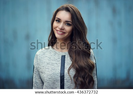 Happy attractive smiling girl portrait against blue old wooden wall. Pretty stylish fashionable woman in gray hoody with long curly hair looking at you. Shallow DOF, blurred background