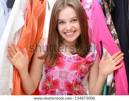 Happy attractive teen girl among clothes in wardrobe or in shop