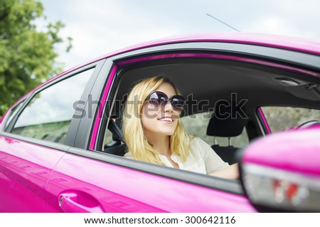 Happy attractive woman driving a new pink car. - stock photo