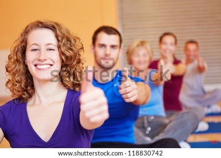 Happy attractive woman in fitness center holding her thumbs up - stock photo