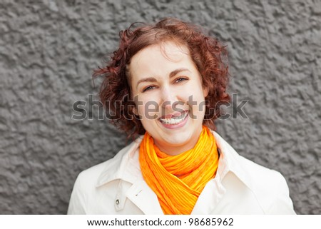 Happy attractive woman leaning on grey wall - stock photo
