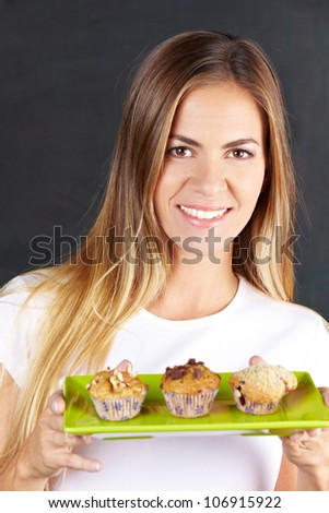 Happy attractive woman offering different muffins in a caf�©
