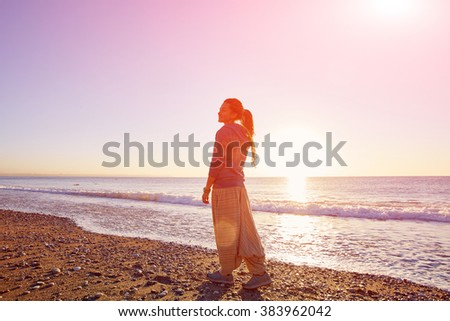 happy attractive  woman walking on the sunny beach over the blue sky - stock photo