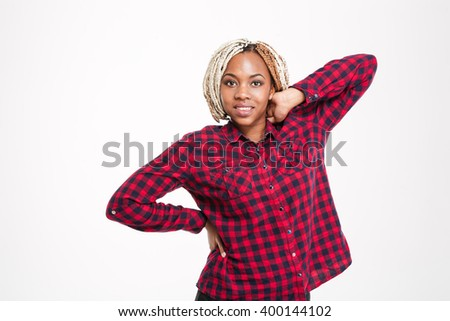 Happy attractive young african american woman in checkered shirt standing over white background - stock photo