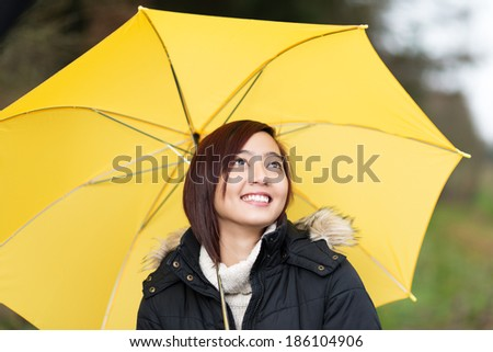 Happy attractive young Asian woman walking with a yellow umbrella looking up at the sky with a lovely smile - stock photo