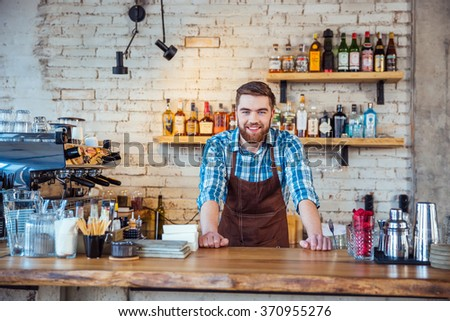 Happy attractive young bearded barista in brown apron at work in cafeteria - stock photo