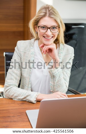 Happy attractive young business woman in eyeglasses with hand on chin working at laptop on smooth wooden desk
