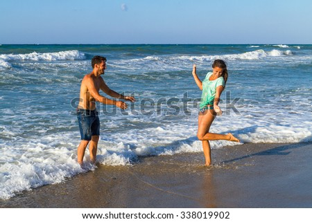 Happy attractive young couple in bikini and shorts enjoying summer dusk at the beach, practicing fitness exercises, having getting wet, kissing and teasing one another.