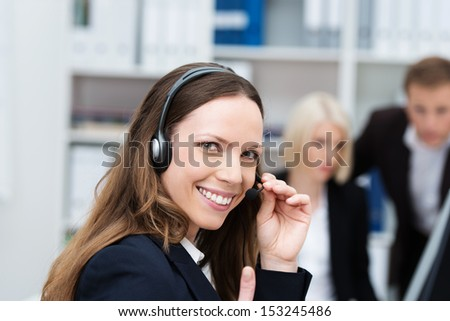 Happy attractive young female call centre operator or receptionist wearing a headset turning to give the camera a friendly smile - stock photo