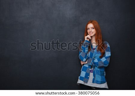 Happy attractive young woman with red hair standing and smiling over chalkboard background - stock photo