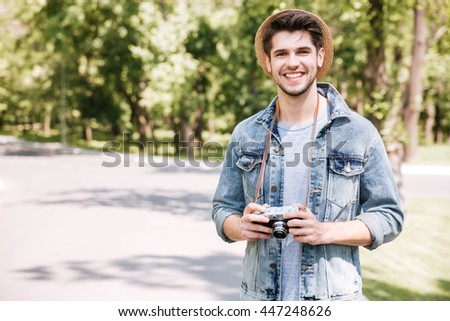 Happy atttractive young man in hat with old vintage photo camera outdoors