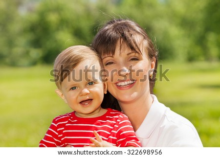 Happy baby and his mummy sitting in green meadow  - stock photo