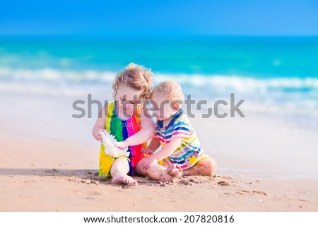Happy baby boy and little curly toddler girl, brother and sister, playing with a huge sea shell in sand on a beautiful exotic tropical beach with turquoise water having fun on vacation - stock photo