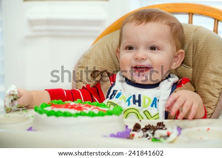 Happy baby boy eating cake for his first birthday party  - stock photo