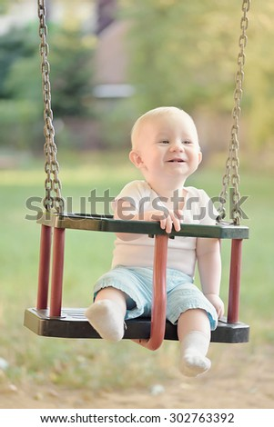 Happy baby boy having fun on a swing ride at a playground a summer day - stock photo