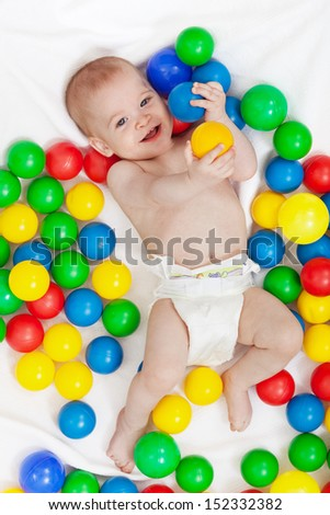 Happy baby boy in diapers with lots of colorful balls playing - stock photo