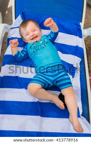 Happy baby boy in swimsuit at the pool - stock photo