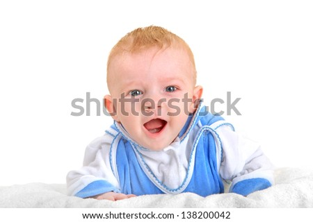 Happy Baby Boy lying on the White blanket and Laughing. Isolated on the White