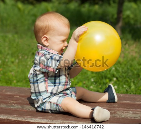 Happy baby boy playing with a ball outdoors - stock photo