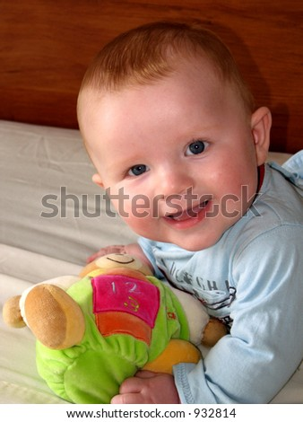 Happy baby boy playing with his toys - stock photo