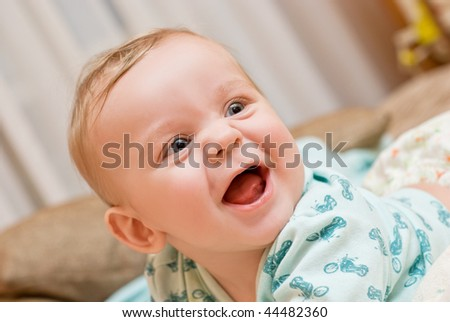 happy baby boy portrait lying at the bed - stock photo