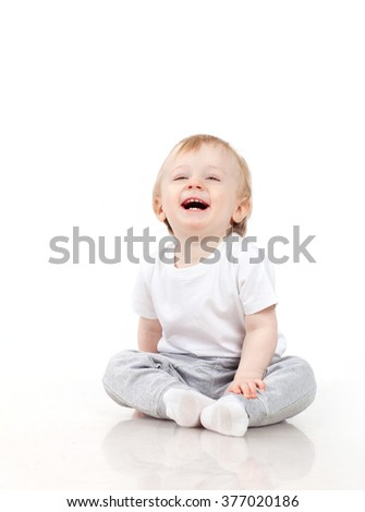 Happy baby boy sitting and laughing