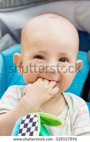 happy baby boy sitting in a blue stroller for a walk - stock photo