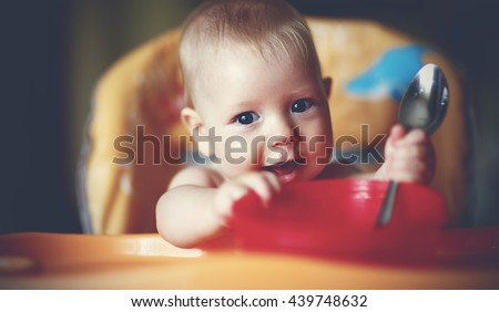 Happy baby boy spoon eats itself - stock photo