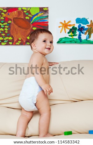 Happy baby boy standing on the sofa lifestyle portrait