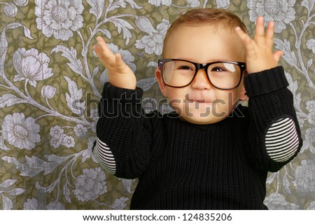Happy Baby Boy Wearing Eye Glasses against a vintage background - stock photo