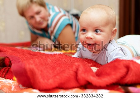 Happy baby boy with his grandmother on a bed - stock photo