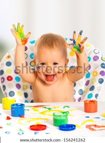happy baby child draws with colored paints hands