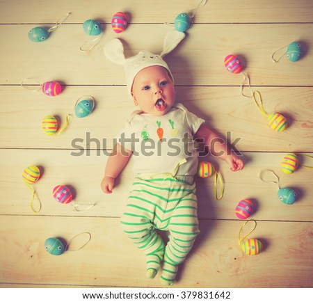 happy baby child  with Easter bunny ears and colorful eggs - stock photo