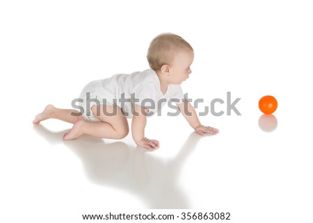 happy baby crawling and playing with small ball toys over white background, motor skill development; side view - stock photo