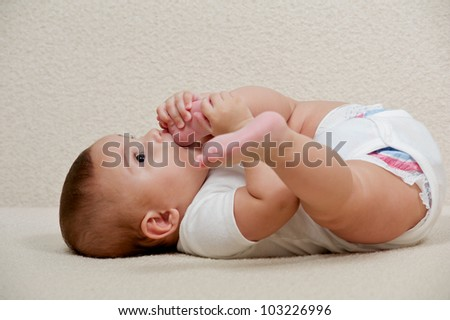 Happy Baby gambling with the feet - stock photo