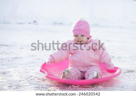 Happy baby girl in a pink hat and jacket, winter outdoor - stock photo