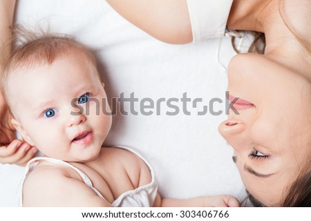 Happy baby girl lying near her mother on a white bed. Newborn looking at the camera and smiling. Mothercare is most important in baby life - stock photo